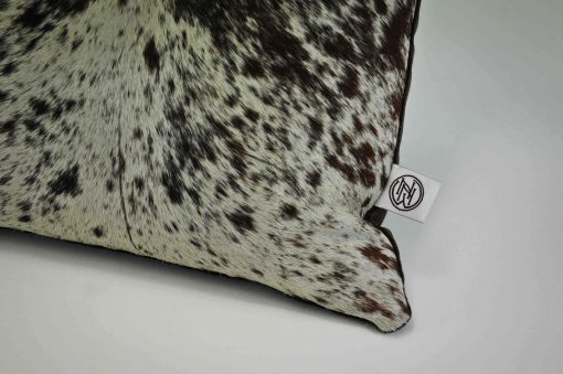 A close up detail of a handmade cowhide scatter cushion by No Naked Windows available on the online shop