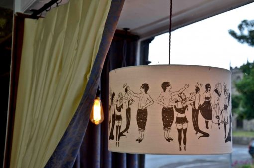 handmade drum lampshade with Naughty Ladies 100% cotton fabric designed by Louise Body displayed in our shop window at No Naked Windows