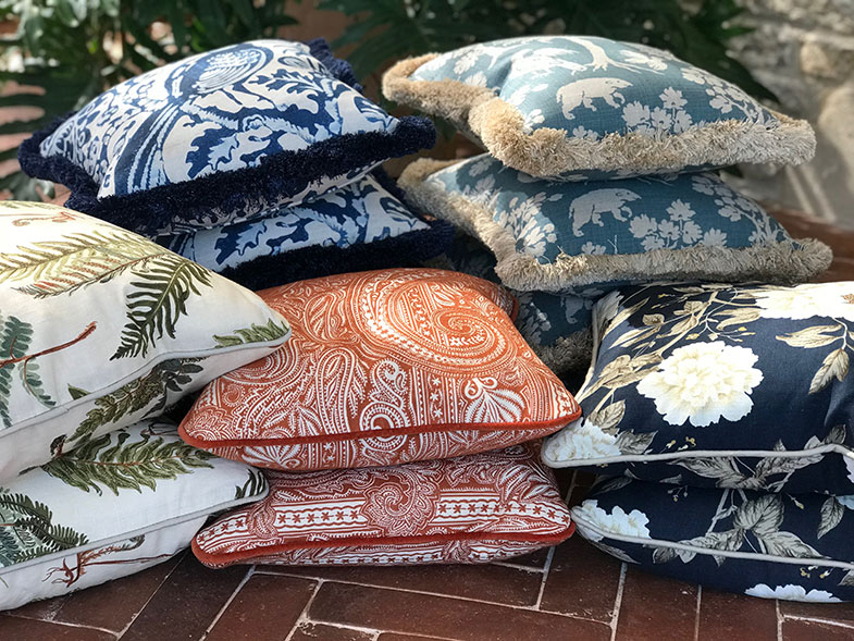 Stacks of designer hand made cushions with various luxury fabric designs and prints