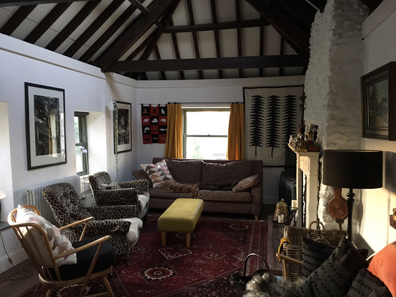 A multi-textural and eclectic sitting room of an artists house in Somerset with soft furnishings and ethnic influences