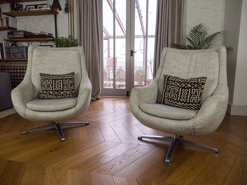 Two vintage swivel egg chairs upholstered in woolen tweed fabric with ethnic black and white throw cushions