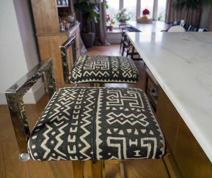 Gold chromed bar stools upholstered in ethnic printed fabric with zigzag pattern