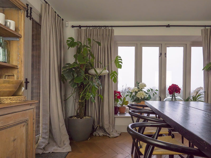 Stunning dining room with full length natural linen curtains with mid century modern dining table and chairs and country pine dresser