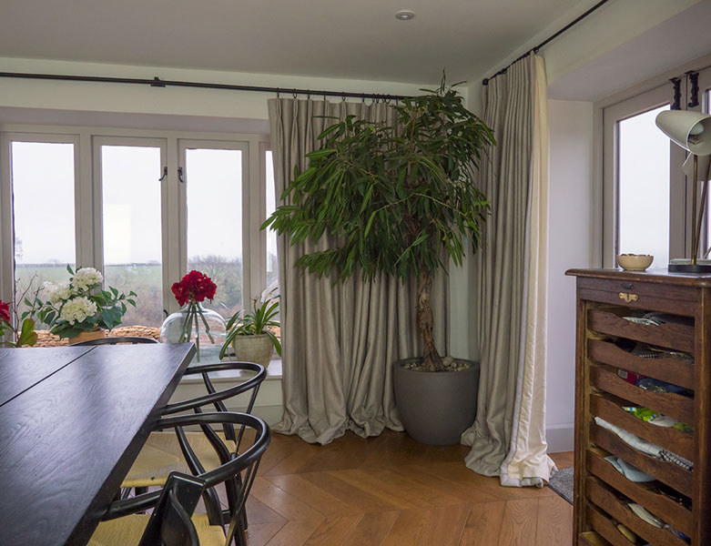 Full length natural linen curtains with mid century modern dining table and chairs