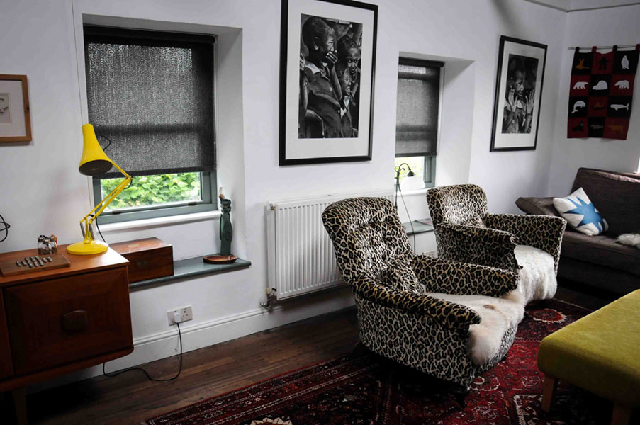 Faux leopard skin upholstered 60's arm chairs in an artists lounge in Somerset