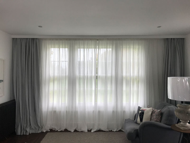 Sheer linen full length privacy curtains teamed with grey linen curtains in a master bedroom suite