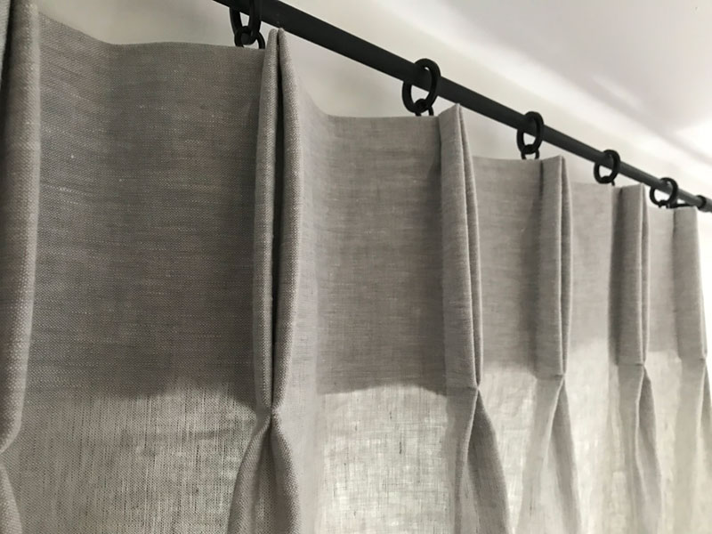 Close up detail of the pencil pleat finish on the tab top of a full length semi sheer linen curtain