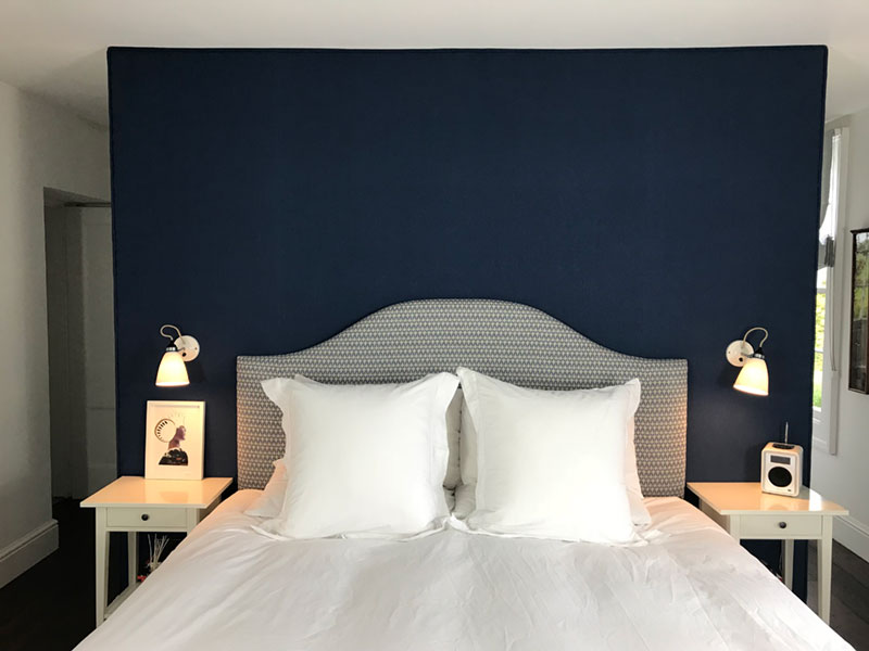 Handmade bespoke upholstered headboard with abstract oval pattern in grey and white with dark navy blue upholstered wall behind in a master bedroom.