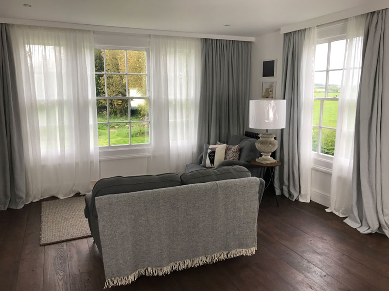 The lounge area of contemporary master bedroom in a Somerset cottage with with full length linen curtains and sheer linen privacy curtains behind.