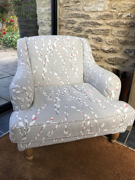 A mid century armchair newly covered and upholstered with grey fabric