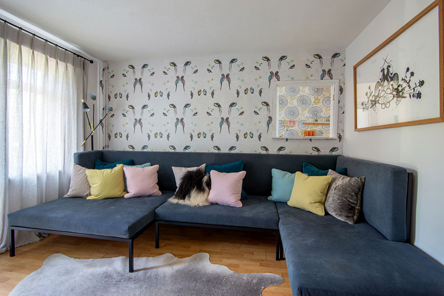 Large bespoke made to measure corner sofa with velvet pink, teal and turquoise scatter cushions. Lounge is decorated with cowhide rug, parrot wallpaper and sheer linen full length curtains.