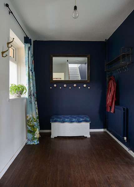 Dark blue entrance hallway with upholstered ottoman and bright full length floral curtains.