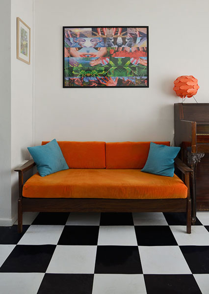 A mid century reclining sofa day bed newly upholstered in bright orange velvet with contrasting teal cushions.