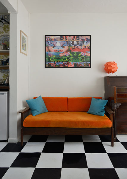 A mid century sofa upholstered with orange velvet