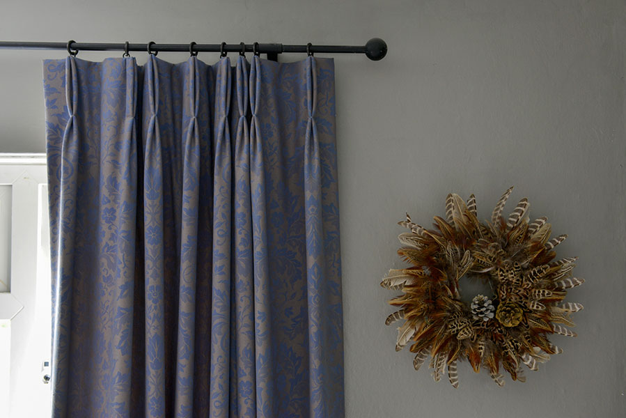 Stunning Damask curtains in blue and grey with a pheasant feather ring on the wall.