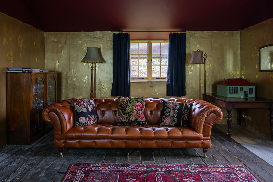 Stunning gold shimmering walls complimented by the dark blue crushed linen curtains in the Hauser & Wirth Farmhouse, Somerset
