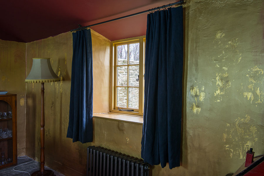 Heavy hand died crumpled linen curtains in darkest navy blue in the gold lounge at Hauser & Wirth Farmhouse, available on AirBnB