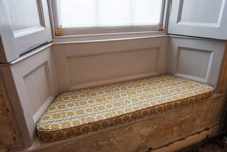 A bay window seat with upholstered cushion seat pad