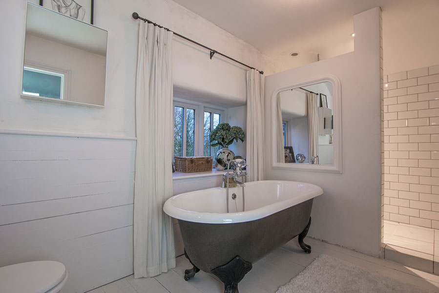 Simple full length white cotton linen curtains behind a roll top bath
