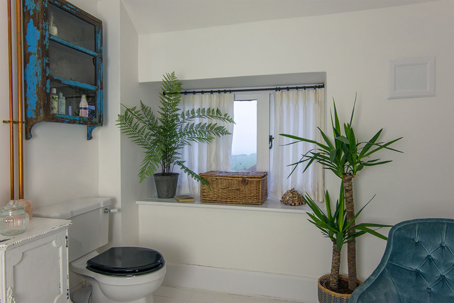 Pretty pleated fine linen curtains in the bathroom with stunning ferns and yukka