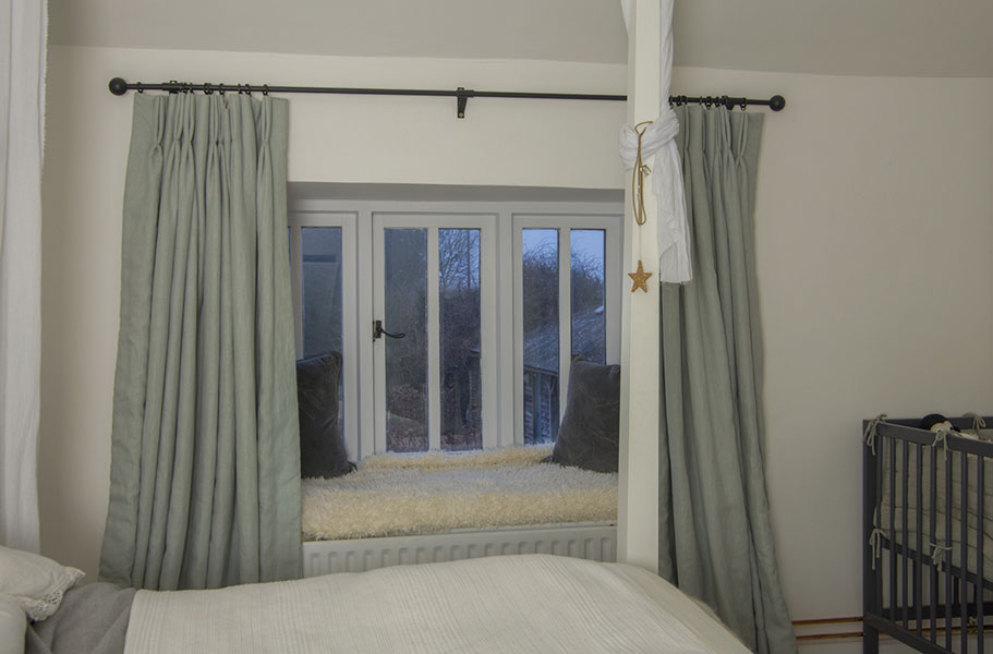 Pinch pleated curtains made from natural linen in a soft grey colour.