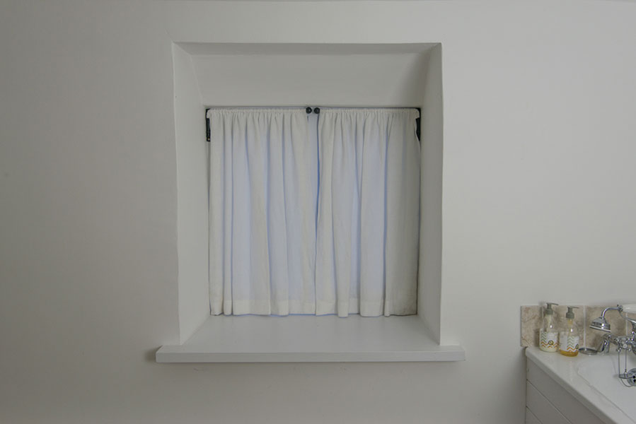 Simple white linen blinds with cast iron hinged fittings.