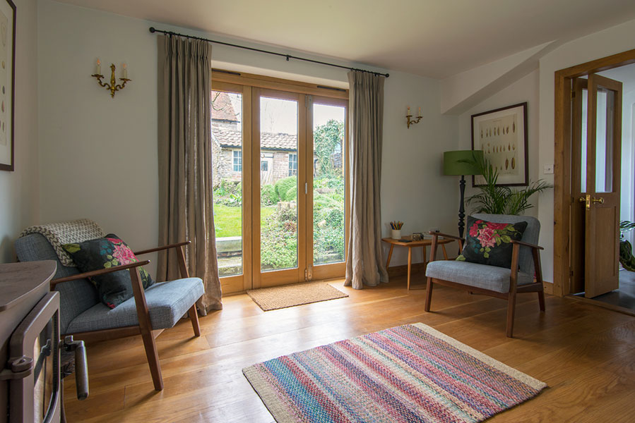 The lounge at Jackdaw Cottage, Bruton, a beautiful AirBNB guest house with linen curtains by No Naked Windows