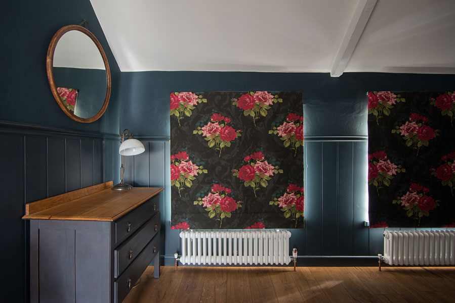 Osborne & Little Rose fabric used for master bedroom. Dark grey background with bright red and pink roses Roman blind pulled down to show window coverage