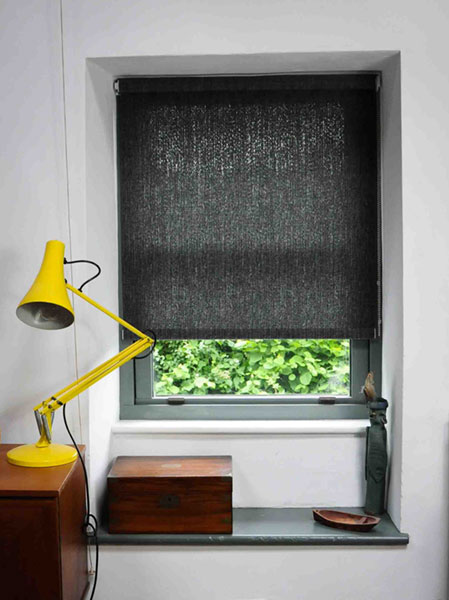 A modern dark grey roller blind with bright yellow anglepoise lamp
