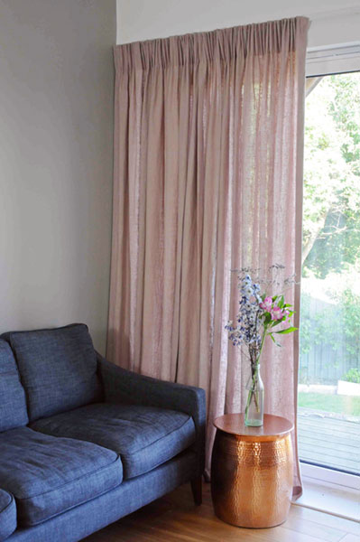 Stunning soft pink semi-sheer linen curtains set off with copper side table