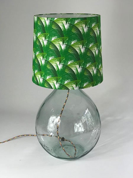 A recycled large statement table or floor lamp with a 100% cotton drum shade with a jungle leaf print in green and white